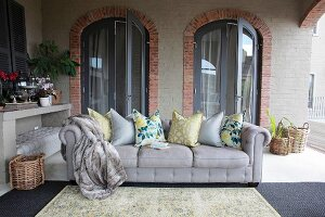 Grey sofa with scatter cushions in loggia