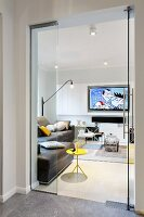View through open glass doors of yellow side table, brown leather sofa and flatscreen TV on wall
