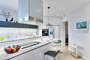 White counter below stainless steel extractor hood and bar stools in designer kitchen