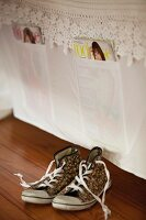 Vintage-style trainers on wooden floor in front of fabric magazine holder made from old bed linen on wall