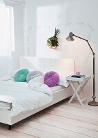 Modern double bed with white headboard and round, colourful scatter cushions; folding bedside table and retro standard lamp
