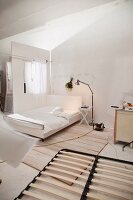 Slated bed frame on floor; white double bed and standard lamp in background