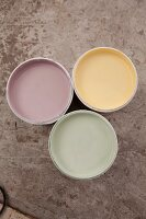 View down onto three open pots of pastel paints