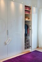 A white wardrobe with an open door and a view of clothing