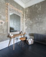 Rustic wooden table and retro stool below mirror with antique frame on patinated wall and decorated with fairy lights