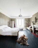 Sleigh bed with slate grey wooden floor in bedroom with free-standing bathtub in background