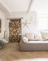 Firewood in niche next to sofa with scatter cushions and white patinated stars on wall