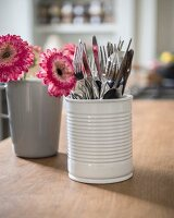 Cutlery in white ceramic beaker and flowers in grey mug on kitchen worksurface