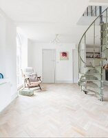 Vintage spiral staircase in open-plan interior with herringbone parquet floor and armchair next to window