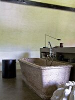 Stone bathtub in simple bathroom with concrete walls and floor