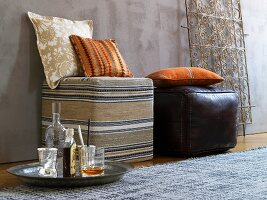 Cushions on pouffes covered in African fabric and leather and ornate metal lattice in background