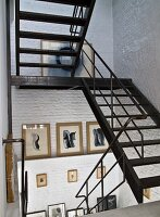 Metal staircase in stairwell with whitewashed brick walls