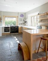 U-shaped kitchen counter and breakfast bar with solid wooden frame in kitchen with pale grey walls