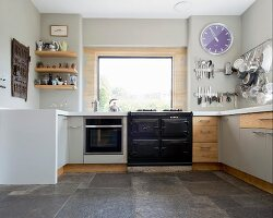 Pale grey, contemporary kitchen with U-shaped counter, integrated AGA cooker and dark grey stone floor