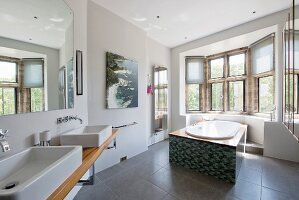 Washstand with twin sinks and modern, free-standing bathtub in window bay of large bathroom