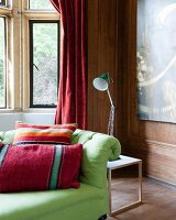 Scatter cushions on green sofa and anglepoise lamp on side table in corner of wood-clad room