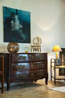 Table lamp on antique chest of drawers below portrait of woman on wall