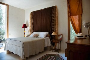 Ethnic-style bedroom with fringed wall-hanging as headbaord