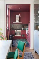 Dining area in front of open doorway leading to dusky-pink kitchen