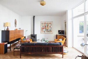 Wooden couch with black leather cushions, side board and fireplace in simple interior
