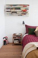 Retro bedside table and bed below modern bookshelf in bedroom