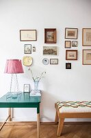Table lamp on green side table and stool below framed pictures on wall