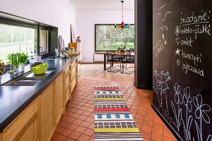 Open-plan kitchen with colourful rug on tiles floor and black wall painted with chalkboard paint