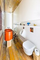 Modern bathroom with toilet, urinal and designer sink made from large, orange saucepan