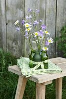 Delicate campanula and ox-eye daisies in green glass bottles on folded green and white tablecloth on rustic wooden stool