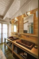 White-painted ceiling and custom washstand with twin sinks against wood-clad wall in bathroom