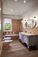 Washstand painted grey-blue, oval mirror, bathtub, toilet and bidet in country-house-style bathroom
