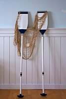 Maritime arrangement of white and blue paddles and fishing net leaning against white wainscoting