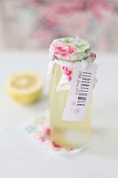 Bottled of home-made elderflower syrup trimmed with lovingly decorated label and rose-patterned fabric