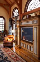 Flatscreen TV integrated into traditional, elegant, country-house interior with arched windows
