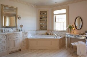 Elegant, country-house bathroom with corner bathtub and dressing table