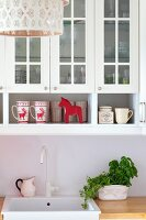 Mugs with reindeer motif below glass-fronted wall units above white sink and potted herbs