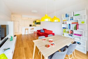 Dining area with yellow pendant lamps in front of bookcase, media centre, red sofa and open-plan kitchen with breakfast bar