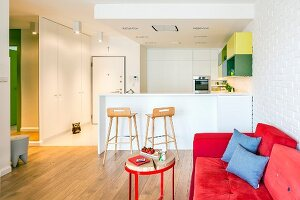 Red sofa and white fitted kitchen with breakfast bar in open-plan living area