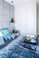 Breakfast tray on double bed with scatter cushions and blanket in shades of blue in bedroom with fitted wardrobes