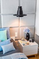 Black pendant lampshade above bedside cabinet against bedroom wall with panelled structure