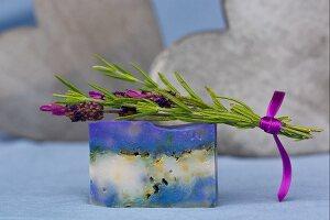 Sprig of fresh lavender on bar of handmade lavender soap