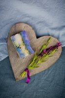 Bar of handmade lavender soap and sprig of fresh lavender on wooden heart