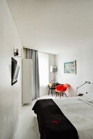 Modern hotel room with double bed, flatscreen TV recessed in wall and red, classic chair next to table in background