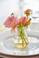 Posy of roses in glass vase on plate