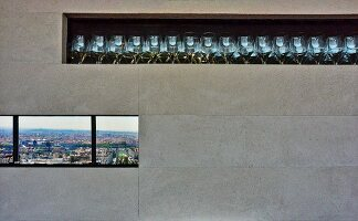 Glasses in stone-tiled niche above ribbon window with view across city