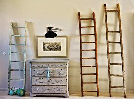 Wooden ladders leaning against wall, old chest of drawers, picture and wall-mounted lamp