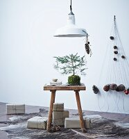 Small pine tree on wooden stool, presents wrapped in brown paper and mobile with pine cone pendants