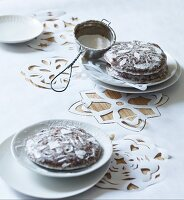 Gingerbread decorated with icing sugar on white tablecloth with cut-out patterns