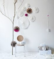 Hand-made, pleated paper stars with cut-out patterns as festive wall decorations
