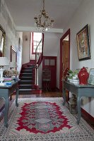 Console tables in foyer of 18th-century, French country house in shades of red and grey